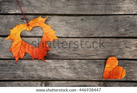 Autumn red and orange leaves with heart.  Fall wooden background.