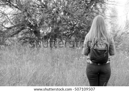 Autumn woman enjoying nature on the field. Beauty hipster in suede leather jacket, plaid shirt, black jeans and backpack outdoors. Boho fashion style. Back view. Black and white