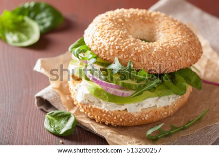 avocado sandwich on bagel with cream cheese onion cucumber arugula