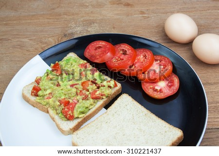 Avocado sauce and whole wheat in black dish on wood