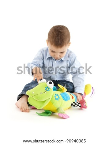 Baby boy busy playing with colorful developmental soft toy.?