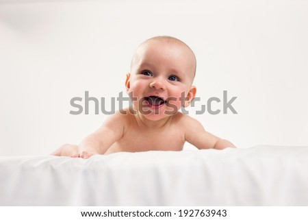 Baby boy on his tummy, smiling on the white background.