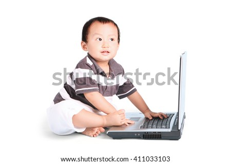 Baby boy playing with a laptop computer, isolated on white background