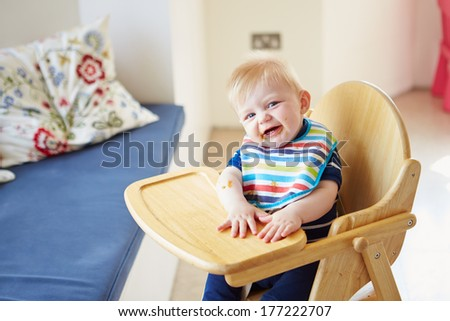 Baby Boy Sitting In High Chair