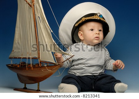 Baby captain in a cap sitting next to sail boat looking up