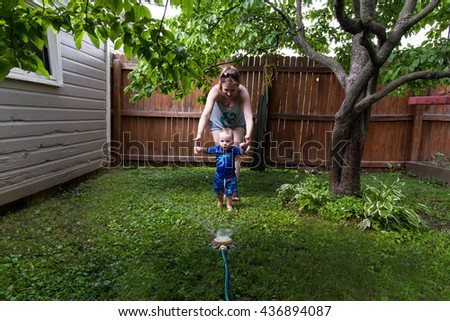 Baby Caucasian Boy and Mother playing in his backyard with a garden sprinkler