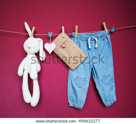 Baby child clothes and goods, blank note or greeting card and toy hanging on clothespins on the clothesline on a textured wall background with copy space. Baby concept background.