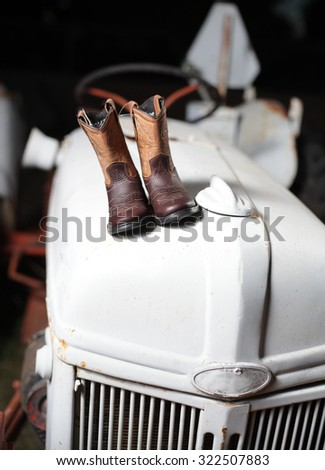 Baby cowboy boots on a white tractor / cowboy boots