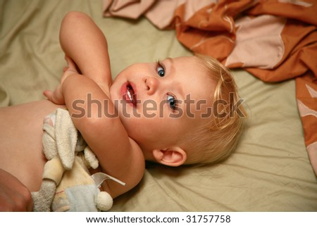 Baby girl crossing her arms on a bed