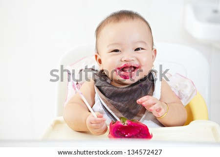 baby girl eating red dragon fruit