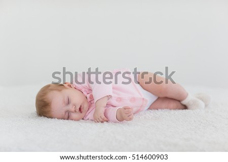 baby girl in a pink sleeping