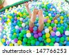 Baby girl playing in playground colourful ball pool - stock photo