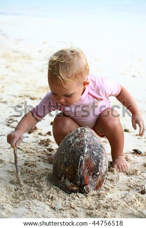 baby girl playing with a coconut