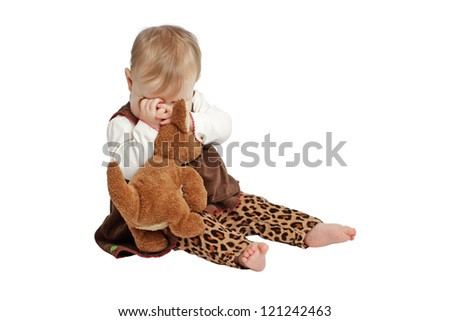 Baby girl sits and plays peekaboo with stuffed animal. She wears a brown velvet embroidered dress with leopard print pants. Isolated/cut out on white background, vertical, copy space.