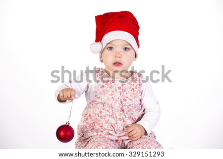 baby girl wearing santa hat on white isolated background with chrismas ball
