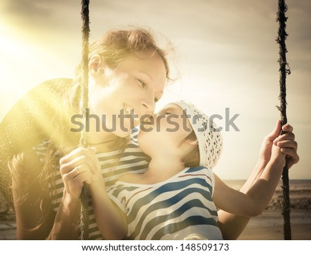 baby girl with her mom on a swing outside.
