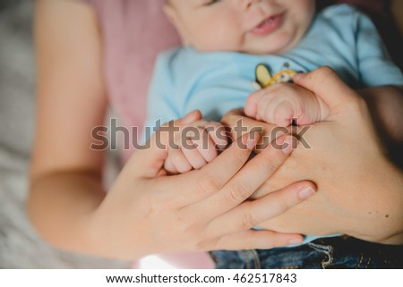 baby hand holding mother