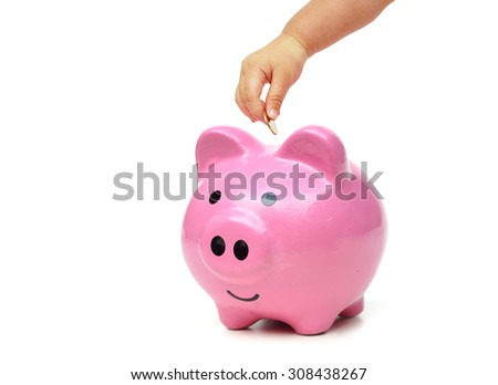 baby hand putting golden coins into a pink piggy