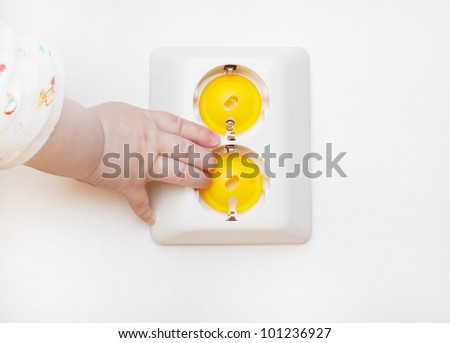 Baby hand reaching for an electrical outlet covered with yellow safety plugs (baby and child safety concept)