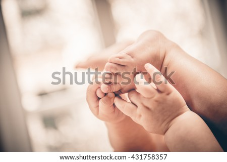 Baby holds his small hands their feet close-up and copy space good as background