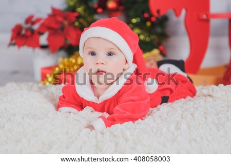 baby in a Santa suit near Christmas tree