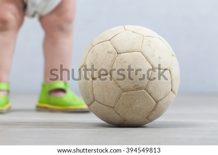 Baby in diaper and sandals in the background of a soccer ball