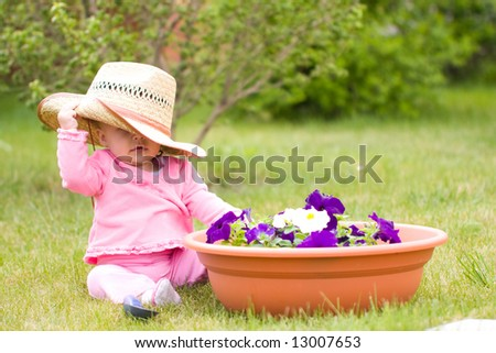 Baby in hat in the garden with flowers