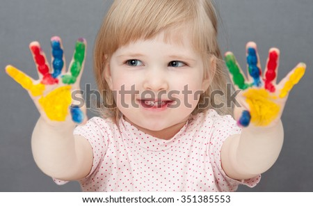 Baby is drawing paint. Grey background