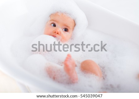 Baby looking upwards in a plastic tub full of foam.