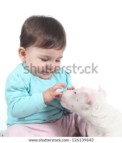Baby playing with a bull terrier puppy on a white isolated background