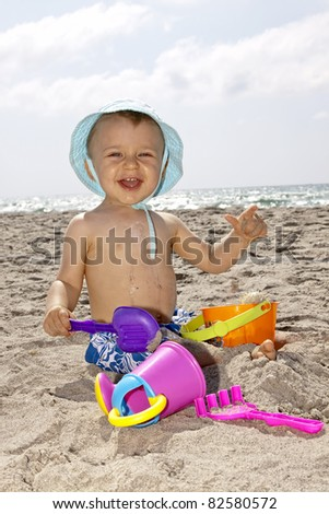 baby playing with toys  on a beach and smiling