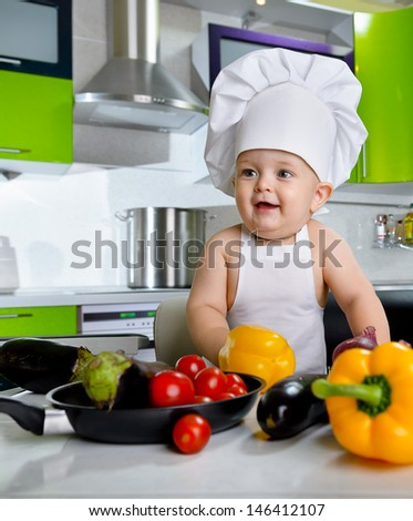 Baby's dressed in a cook costume in the kitchen
