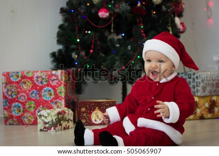 Baby sitting in a suit of Santa Claus at the Christmas tree with gifts