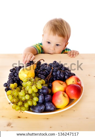 Baby with dish of fruit on the table, isolated on white