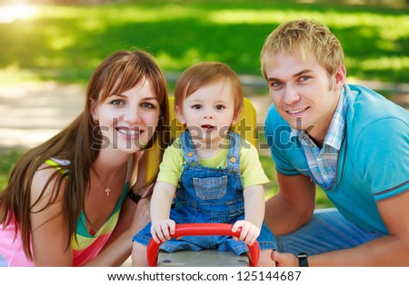baby with parents in a green  park
