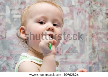 baby with spoon in hands