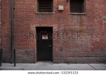 Back door entrance to an old brick building from the alley.