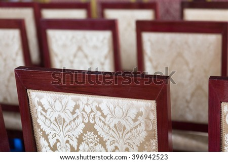 back of beige cushion with flower pattern decorating with wooden brown red chair