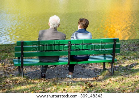 Back of senior couple sitting at the lake