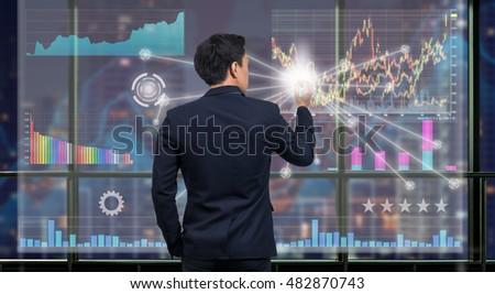 Back side of Businessman drawing the Technical information and trading graph over the virtual screen on the blurred of cityscape background out off windows, Business financial concept