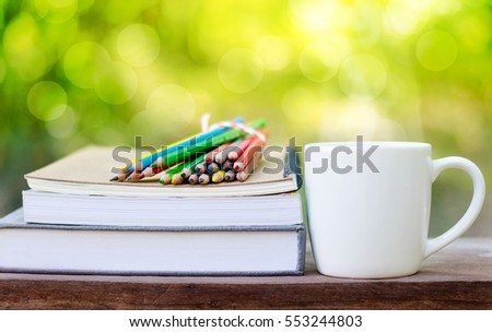 Back to School concept, Coffee cup with book and color pencils over nature green background