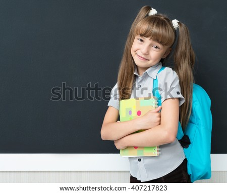 Back to school concept. Happy schoolgirl with backpack at the black chalkboard in classroom.