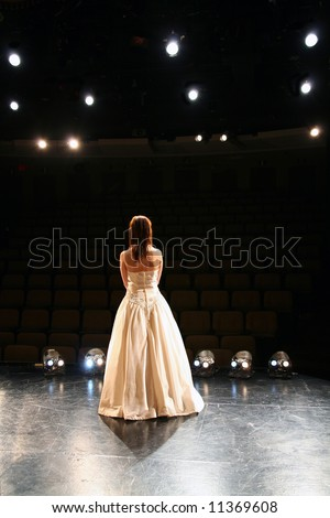back view girl in long gown performing on stage