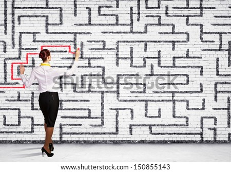 Back view image of young businesswoman trying to find way in labyrinth