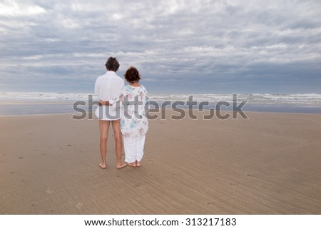 Back view of a couple sit on beach