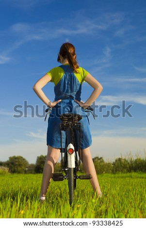Back view of a womanl over her bicycle, in a green meadow