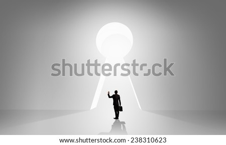 Back view of businessman standing in keyhole doorway