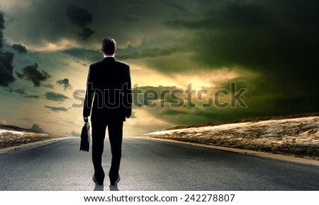 Back view of businessman standing on road and looking far away
