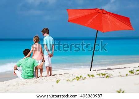 Back view of father and kids enjoying beach vacation