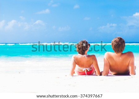 back view of happy young caucasian couple sitting at the beach